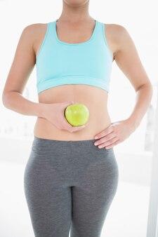 Woman in sportswear holding green apple