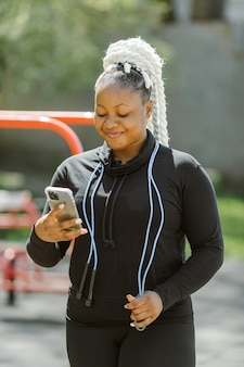Donna in abiti sportivi che tiene uno smartphone