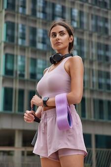 La donna in abbigliamento sportivo tiene il karemat di gomma della fascia fitness si prepara per la ginnastica che si esercita rimane in forma e si alza in piedi sani contro l'edificio di vetro sfocato in luogo urbano