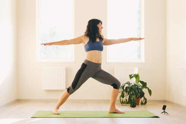 A woman in sportswear is doing a workout at home - a girl is engaged in fitness while watching a workout via video communication