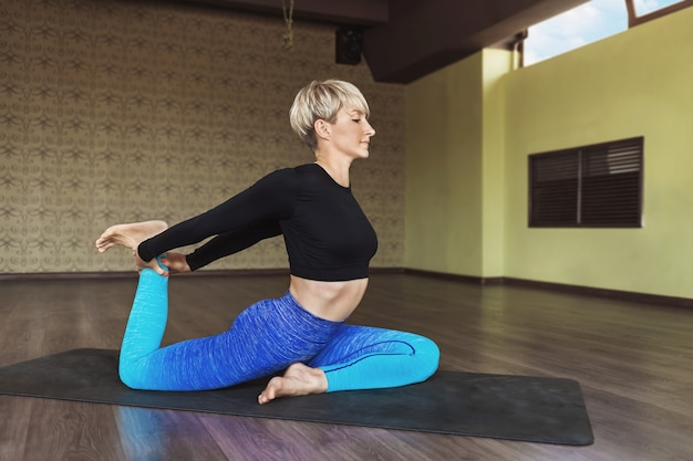 A woman in sportswear is doing yoga in a room by the window sitting on a mat