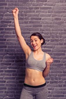Woman in sportswear is holding hands in fists.