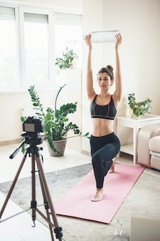 Woman in sportswear is stretching in front of camera using a water bottle at home during digital lessons