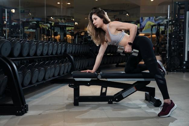 Woman in sportswear is training in the gym
