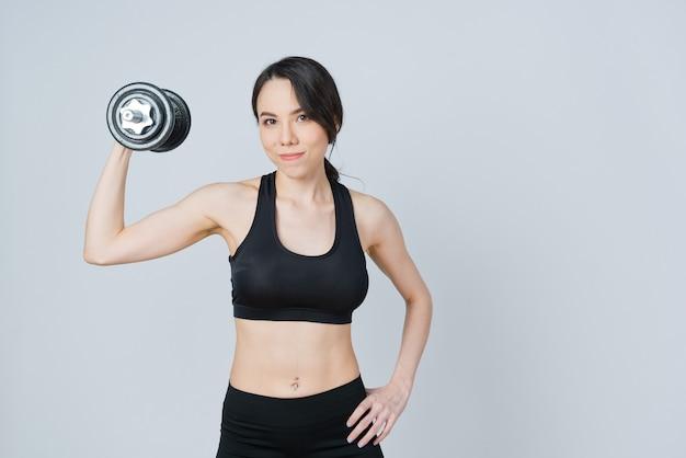 Woman in sportswear lifting a dumbbell