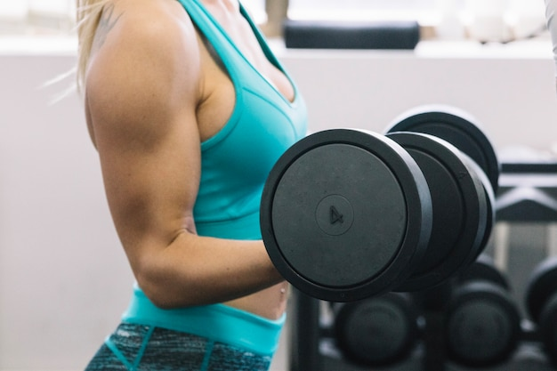 Woman in sportswear lifting dumbbells
