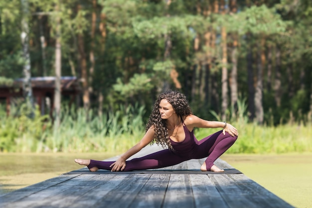 A woman in sportswear practicing yoga in the park performs a side lunge