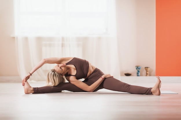 Woman in sportswear practicing yoga performs an exercise with head turning to her knees parivritta janu shirshasana exercising in the studio while sitting on a mat