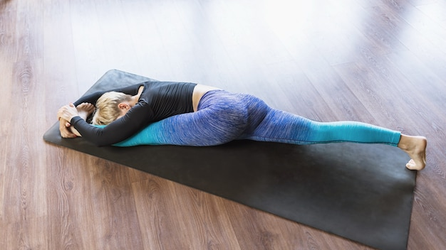 A woman in sportswear practicing yoga performs hanumanasana exercise on a mat in the studio a longitudinal split with the head tilted to the leg