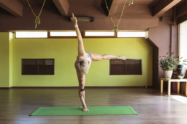 A woman in sportswear practicing yoga performs a variation of the ardha chandrasana exercise the crescent moon pose