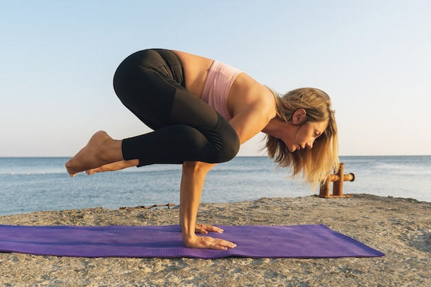 A woman in sportswear practicing yoga on the seashore performs the kakasana exercise, crow pose