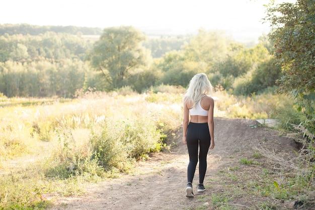 Спортивная одежда женщины работает на холме