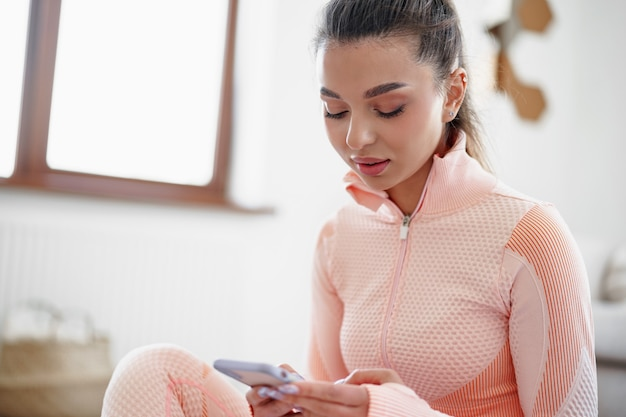 Woman in sportswear sitting indoors and looking at smartphone before workout