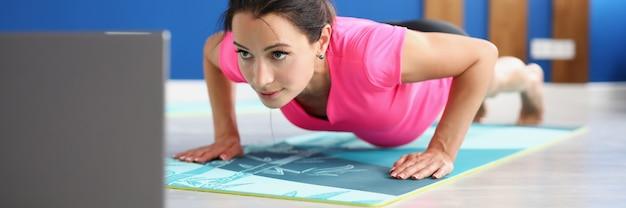 Woman in sportswear standing in plank on floor in front of laptop