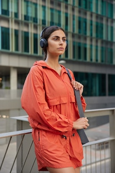 Woman in sportswear waits for coach outdoors has break after workout or jogging exercises every day to be healthy rests and looks forward enjoys favorite playlist