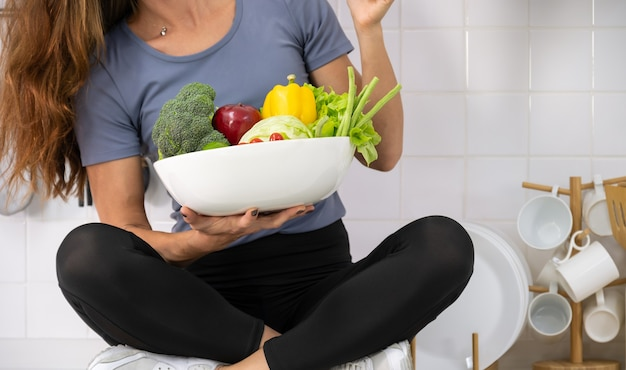 Woman in sportswear with white bowl of  fresh mixed vegetables in her hand.