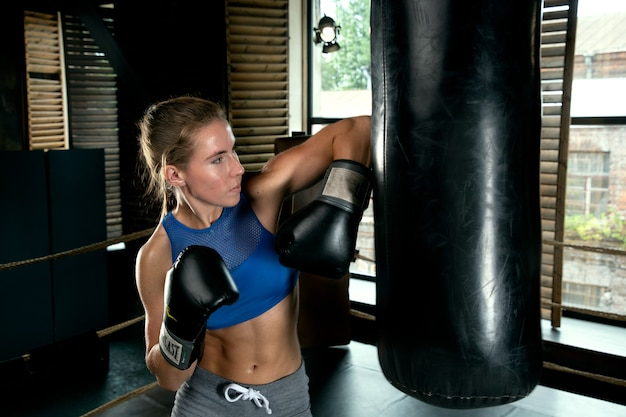 Woman sportswoman beats the pear with her elbow