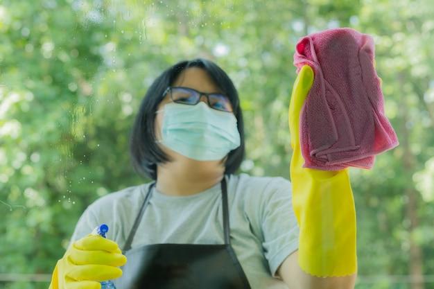 Женщина распыляет и протирает стекло