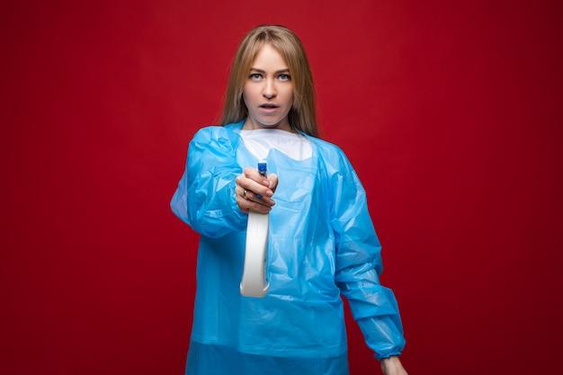 女性がカメラで消毒剤を散布します。ウイルスの概念を停止します。