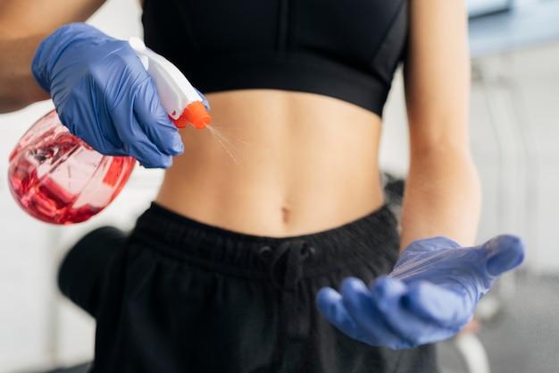Женщина распыляет дезинфицирующее средство на перчатки в тренажерном зале