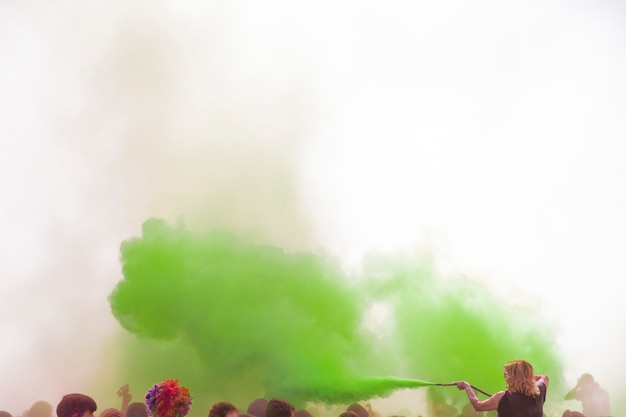 Woman spraying the green holi color with pipe over the crowd
