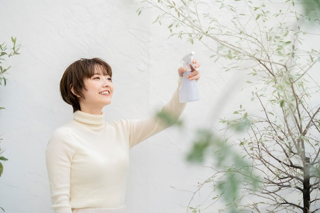 Woman spraying water on plants in the garden of the house