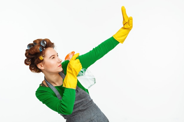 Woman spraying windows and posing with yellow rubber on hands