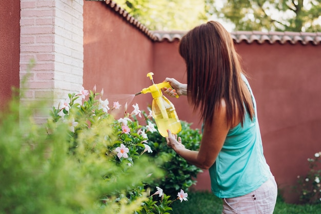 Woman spraying with aphid repellent liquid on flowers
