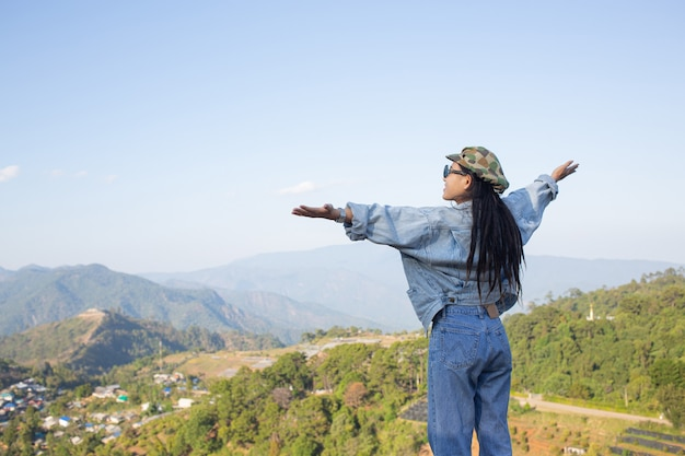 高い木の自然林の真ん中に腕を広げた女性