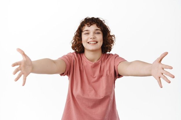 Woman spread hands sideways and smiling, hugging someone, reaching for embrace and cuddles, welcome and greet friend, standing on white