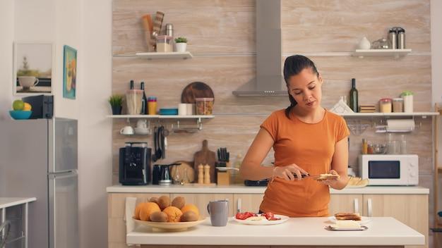 朝食にトーストしたパンにバターを塗る女性。パンのスライスに柔らかいバターを塗るナイフ。健康的なライフスタイル、居心地の良いキッチンで朝のおいしい食事を作ります。伝統的なおいしいランチ