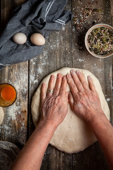 Woman spreading dough with hands on wooden table top view.