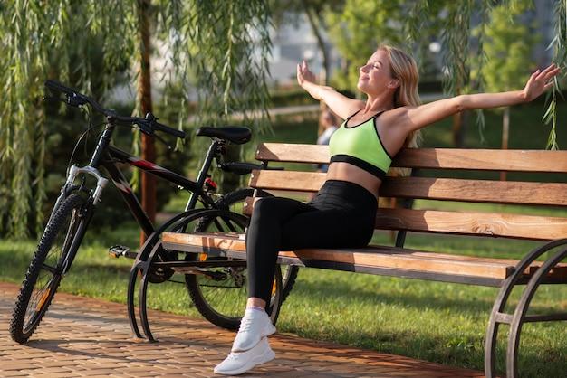 Женщина раздвигает руки и сидит на скамейке