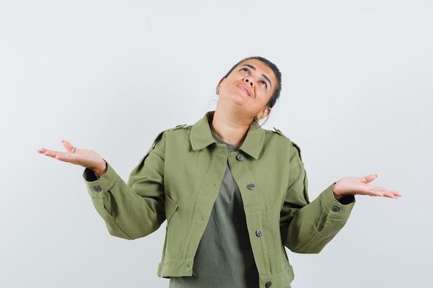 Женщина разводит ладони, глядя вверх в куртке, футболке и выглядит благодарной