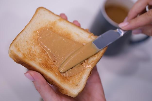Woman spreading peanut butter on toast closeup