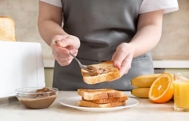 여자는 아침에 토스트에 땅콩 버터를 퍼뜨립니다. 토스트, 주스, 과일로 구성된 유럽식 조식.