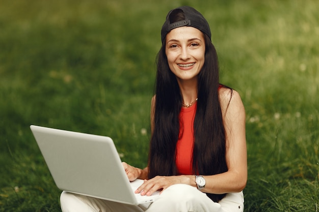 Woman in a spring city. lady with a laptop. girl sitting on a grass.