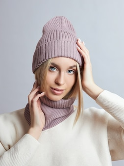 Woman in spring clothes, snood scarf, hat and gloves. the girl is blonde with blue eyes. warm clothing for cold spring weather
