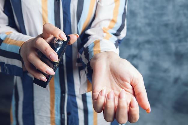 女性が手に香水を振りかける