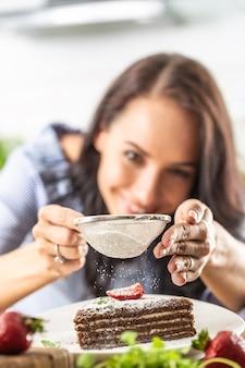 여자는 얇게 썬 케이크 위에 가루 설탕을 뿌린다.
