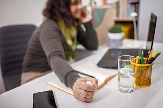 オフィスでのストレスを軽減するために彼女の手で抗ストレスボールを押しつぶす女性