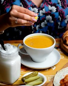 Женщина сжимает лимон в суп из чечевицы