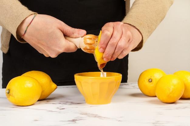 木製のスクイザーで半分レモンを絞る女性