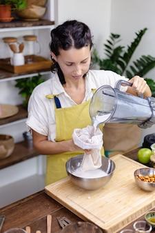 Женщина выжимает миндальное молоко из миндаля на кухне дома