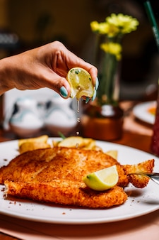Woman squeezing lemon on crispy fries fish