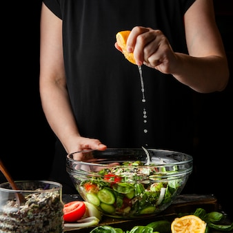 Woman squeezing lemon into chunky salad side view.