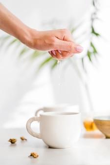 Женщина сжимает лимон над чашкой