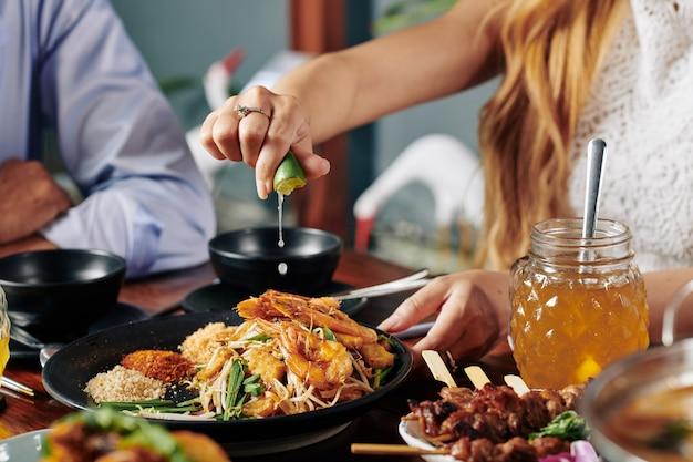 Женщина, выжимающая лайм в блюде