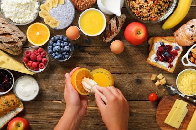 Woman squeezing orange fruit and making juice. granola, nuts, fruits, berries, milk, yogurt, juice, cheese.