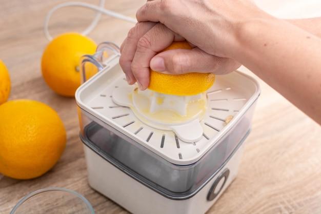 Женщина сжимает апельсины на кухне
